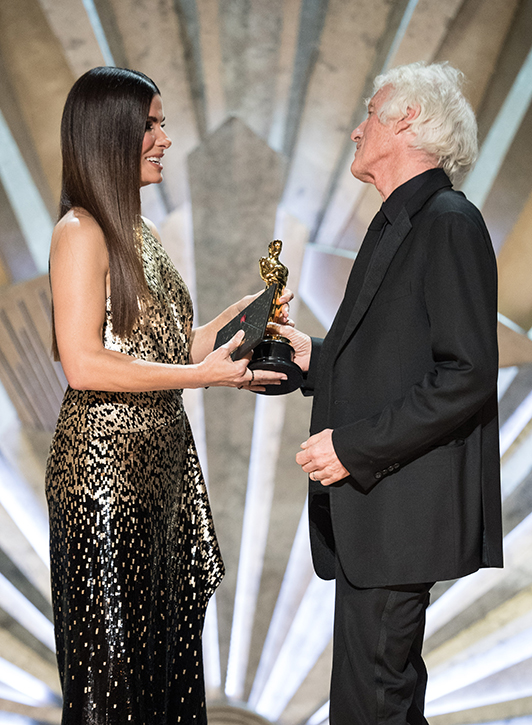 Sandra Bullock presents the Oscar for achievement in cinematography to Roger A. Deakins
